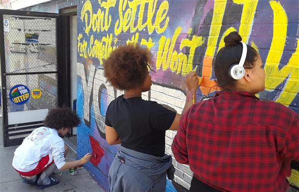 Students painting mural on local convenience store