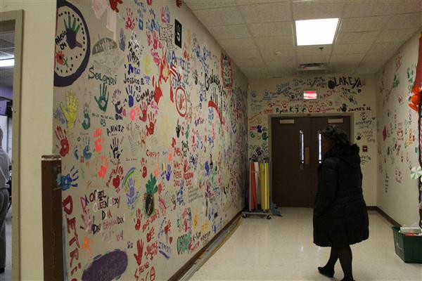Students who have graduated mark their legacy with a handprint on the wall.