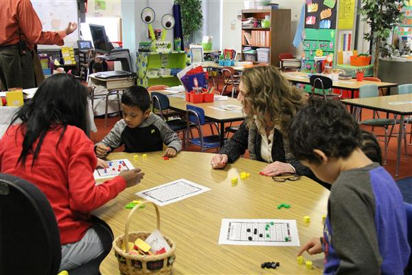 Superintendent Barbara Deane-Williams learns how to play a math game from the students.