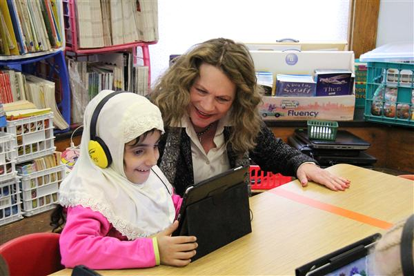 A student shows the Superintendent how her interactive iPad game works